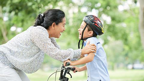 Mom teaching child to ride bicycle