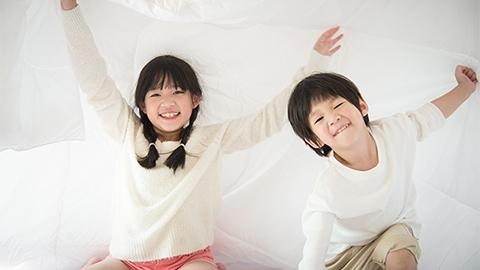 Siblings playing on bed
